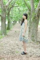 並木道に立つ日本人女性 10272002552  写真素材・ストックフォト・画像・イラスト素材 アマナイメージズ