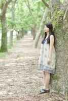 木にもたれてに立つ日本人女性 10272002558  写真素材・ストックフォト・画像・イラスト素材 アマナイメージズ