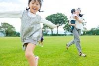 芝生を走る日本人の家族