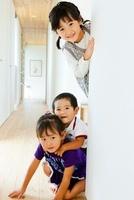 壁から顔を覗かせる3人の子供 10272002605  写真素材・ストックフォト・画像・イラスト素材 アマナイメージズ