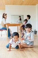 床に座る子供とティータイムの母親達