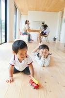 玩具で遊ぶ子供とティータイムの母親達