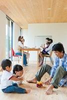 玩具で遊ぶ父親と子供とティータイムの母親達