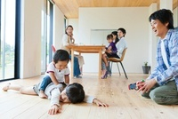 床で遊ぶ父親と子供とティータイムの母親達