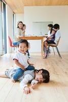 床で遊ぶ子供とティータイムの母親達