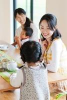 テーブルを囲んで笑う母親と子供