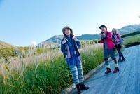 湿原に立ちトレッキングを楽しむ日本人女性