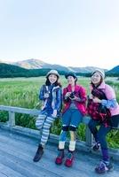 カメラを待って柵に座る日本人女性