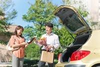 車の後ろで荷物を渡す日本人カップル