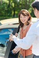 車の前に立つ日本人カップル