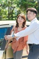 車の前に立つ日本人カップル 10272002802| 写真素材・ストックフォト・画像・イラスト素材|アマナイメージズ