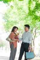 新緑の下で笑う日本人カップル