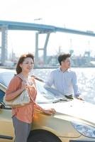 車の前に立つ日本人カップル 10272002857| 写真素材・ストックフォト・画像・イラスト素材|アマナイメージズ