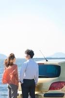 車の後ろに立つ日本人カップル 10272002863| 写真素材・ストックフォト・画像・イラスト素材|アマナイメージズ