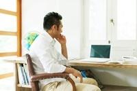 パソコンに向かって座る日本人の男性