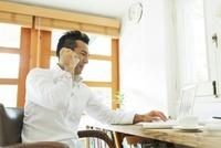 電話をしながらパソコンをする日本人の男性