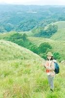 リュックを背負って山にたたずむ日本人女性