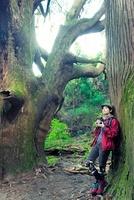 木にもたれカメラを持って立つ日本人女性
