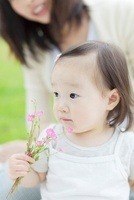 花を持つ日本人の女の子と母