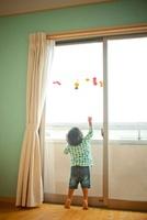 ハロウィンの格好をして窓辺に立つ兄弟