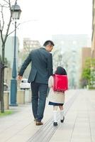 手を繋いで歩く日本人の父と娘の後ろ姿
