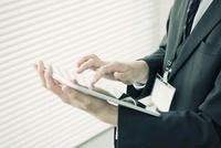 タブレットPCを操作するビジネスマンの手元