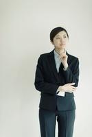 指をあて考える日本人ビジネスウーマン