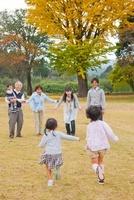 紅葉の広場で遊ぶ三世代家族