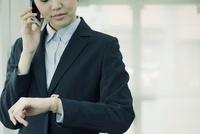 電話をしながら腕時計を見るビジネスウーマン