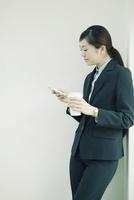 スマートフォンを操作するスーツ姿の女性