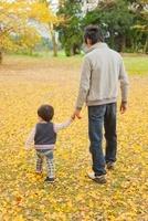 落ち葉の上で手をつないで歩く親子