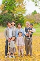 落ち葉の上に立つ三世代家族