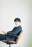 椅子に座りタブレットPCを持つビジネスマン