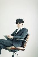 椅子に座りタブレットPCを見るビジネスマン