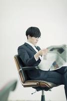 椅子に座り新聞を読むビジネスマン