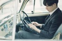 車でタブレットPCを見るスーツ姿の男性