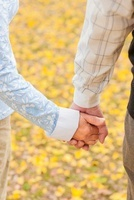 手を繋ぐシニア夫妻の手元