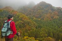 山に佇むトレッキングをする男性