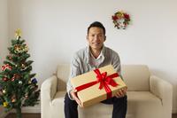 ソファに座りプレゼントボックスを持つ男性