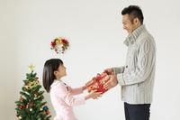クリスマスプレゼントを渡す父と娘