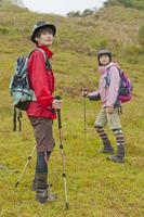 山に佇むトレッキングをする男女