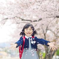桜の花びらをまく新入学の女の子