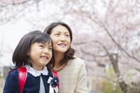 桜の木の下で微笑む女の子と母親