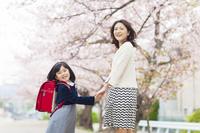 桜並木の下に立つ新入学の女の子と母親