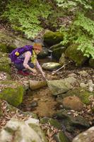 渓流に手をつけるリュックを背負った女性