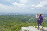 岩の上に立ち写真を撮るトレッキングの女性