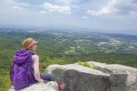 岩の上に座るトレッキングの女性