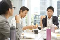 テーブルを囲みランチを食べる3人の男性
