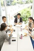 テーブルを囲みランチを食べる男女