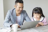 ノートパソコンを見る日本人の父と娘
